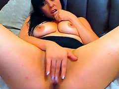 Busty brunette masturbates with a dildo on the couch