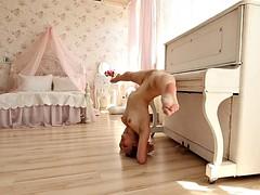 acrobatic hottie nino belover shows her skills near the piano