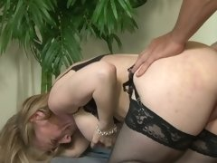 A blonde mature lady is placing her lips around a large dick