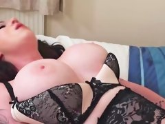Busty woman in stockings is massaging her pussy with a toy