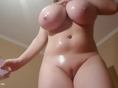 Busty brunette mature mom oils up her naked curvy body and big melons